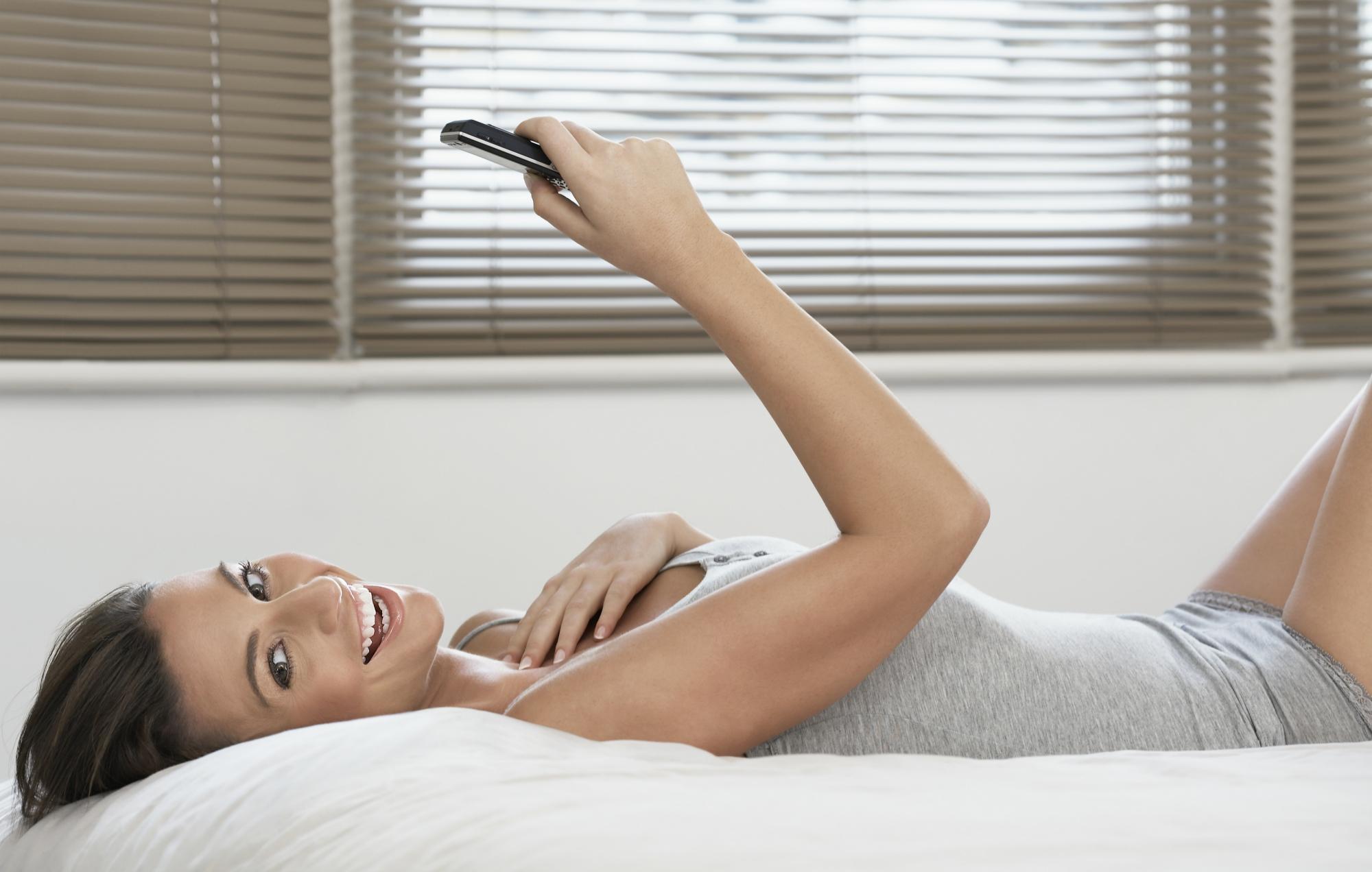 Kvinde ligger i sengen med telefon i hånden